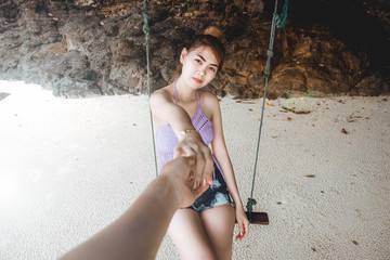 Closeup Young woman in bikini holding man hand while sitting on swing at beach. Couple in love