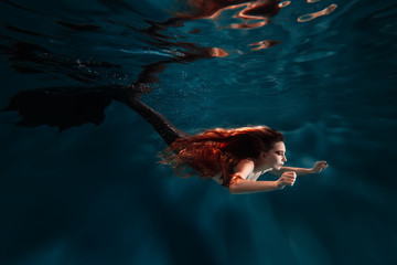 Swimming underwater red hair freediver girl with mermaid tale