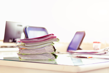 Stack of documents placed on a business desk in a business office.