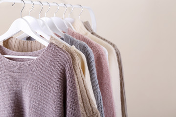Wall Mural - Warm knitted clothes hanging on a rack