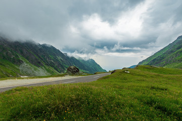 transfagarasan road in stormy weather. popular travel destination of romania. grassy meadow along on the edge of a hill. view in to the distant valley. overcast sky