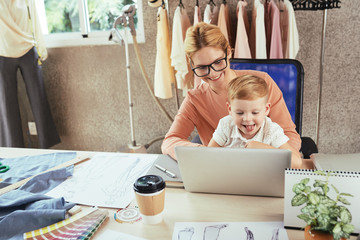 Cheerful female fashion designer working on laptop with son on her laps