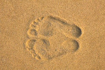 two foot prints on yellow sand close up