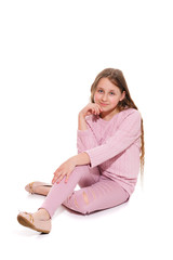 A smiling girl in a pink suit is sitting on the floor. Isolation on a white background.