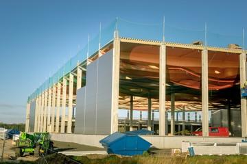 Rohbau einer großen Industriehalle mit Sicherheitsnetzen auf dem hohen Flachdach