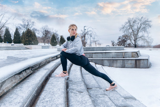 fitness girl climbs the stairs, sport, exercising, training on city street over snow