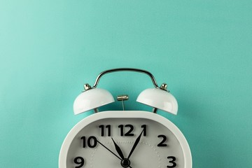 white vintage alarm clock on blue background. - top view.