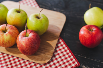 group of apples on wooden cutting board with napkin
