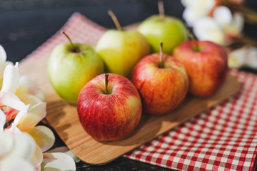 group of apples on wooden cutting board with napkin and flowers