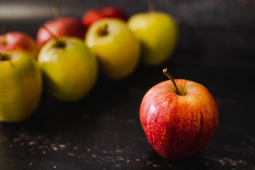 apples lines up and one red one standing out in front of them on its own