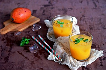 Mango lassi, traditional Indian drink in glasses. Served with ice and straw.
