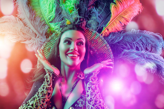 Beautiful young woman in carnival peacock costume. Beauty model woman at party over holiday background with magic glow. Christmas and New Year celebration. Glamour lady with perfect make up and