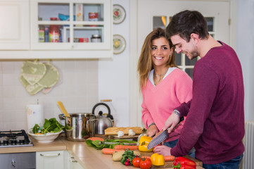 Loving and happy couple cooking vegetables in the kitchen at home