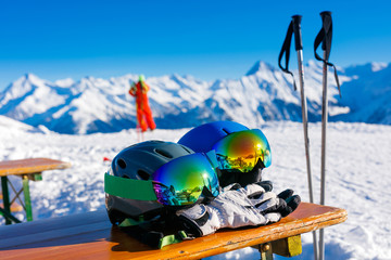 Colorful ski glasses, gloves and helmet on wooden table.