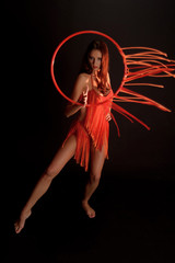 sexy dancer in red with a hoop on a black background