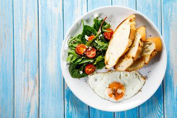 Breakfast - fried egg, toasts and vegetable salad