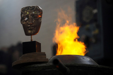 A completed British Academy of Film and Television Awards (BAFTA) mask is placed next to a furnace to be photographed at a foundry in west London