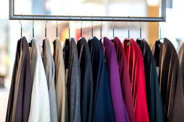 Clothing jersey cashmere items on a rack in fashion store. Capsule wardrobe, winter spring sale
