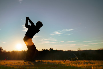 Young junior golfer practicing in a driving range with beautiful sunset light in winter.