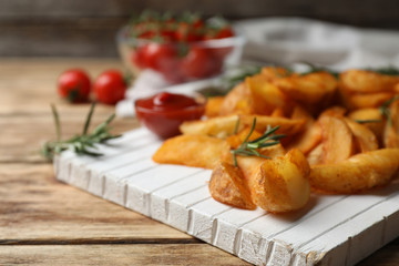 Wooden board with baked potatoes and rosemary on table, closeup