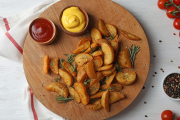 Baked potatoes served with rosemary, ketchup and mustard on table, top view