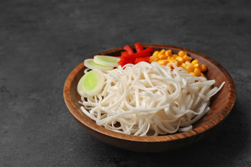 Plate with rice noodles and vegetables on table
