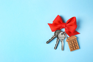 House keys with trinket and bow on color background, top view. Space for text