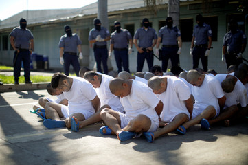 Mara Salvatrucha (MS-13) gang members wait to be escorted upon arrival at the maximum-security jail in Zacatecoluca