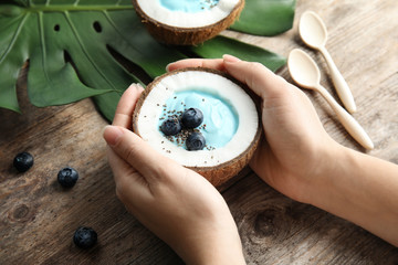 Woman holding coconut with spirulina smoothie on wooden table, closeup