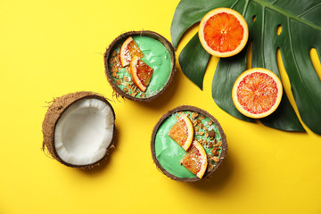 Coconut shells with yummy spirulina smoothie on color background, top view