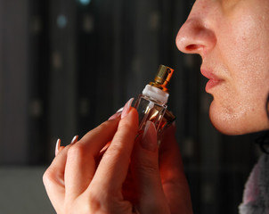 Young woman smelling perfume from a bottle, nail art on hers nails