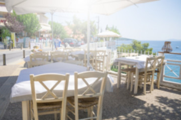 Restaurant tables and chairs below the sunshade on the terrace on the seashore. Blurred scene of the restaurant in Neos marmaras, Greece.