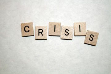 Crisis spelled in black letters on a white background. Wooden blocks are staggered.