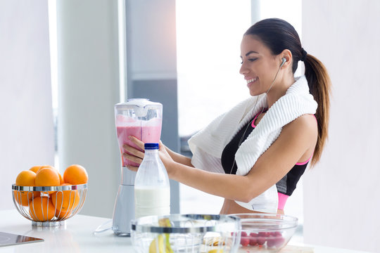 Sporty young woman preparing strawberry and banana smoothie with blender in the kitchen at home.