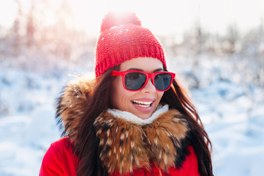 Smiling woman with red sunglasses on winter background