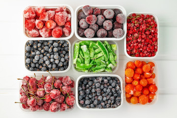 Top view frozen vegetables and berries in plastic containers