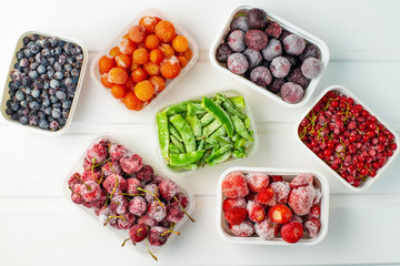 Frozen berries and vegetables in plastic boxes on white wooden background