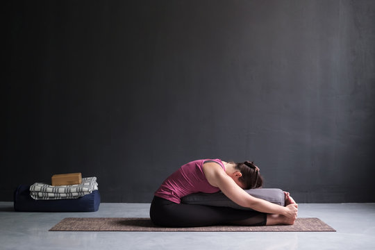 woman practicing yoga, doing Seated forward bend pose, using bolster.