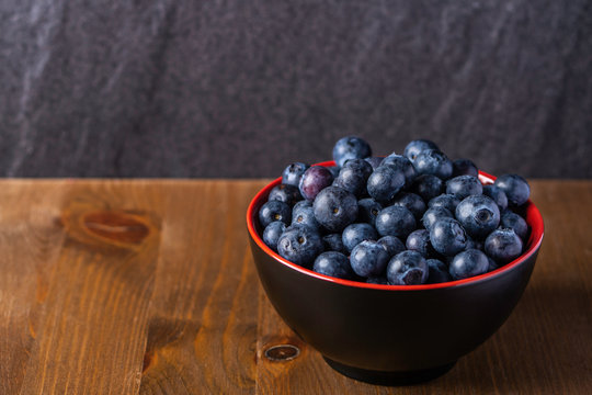 A close up shot of fresh organic blueberries in a red bowl with a wooden base and a rock background