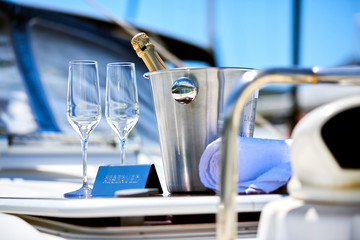 Romantic luxury evening on cruise yacht with champagne setting.Empty glasses and bottle with champagne and tropical sunset with sea background