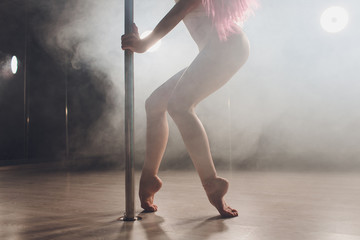 Red haired pole dance girl exercises and poses on the pylon in the smoke on the black background.