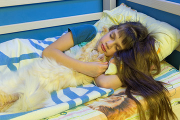 Girl sleeping in a crib with a fluffy cat