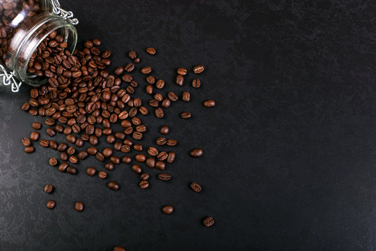 Fragrant coffee beans are scattered from a jar on a rustic tabletop background. Banner copy space.