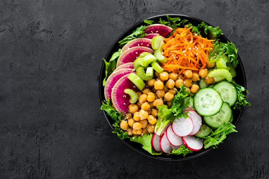 Salad Buddha bowl with fresh cucumber, celery, watermelon radish, raw carrot, lettuce, radish and chickpea for lunch. Healthy vegetarian food. Vegan vegetable dish. Top view