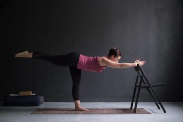 Woman show warrior asana using chair in studio background