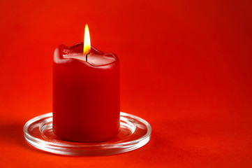 red burning candle on a red background