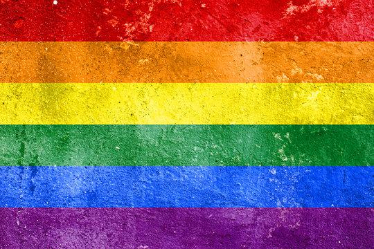Rainbow flag on concrete wall. Symbol of sexual minorities and tolerance.