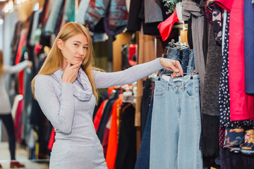 Woman with jeans and shopping in a fashionable clothing store.