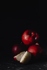Red apples and slices of apples. Dark. Baton background. Photo in low key. Place fot text, copy paste space