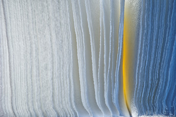 Background of porous paper, illuminated with blue and yellow LED lamps. Texture and abstraction